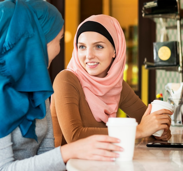 Islamitische vrouwenvrienden die en in de koffiewinkel genieten van spreken