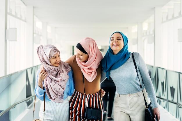 Islamitische vrouwenvrienden die en samen lopen bespreken