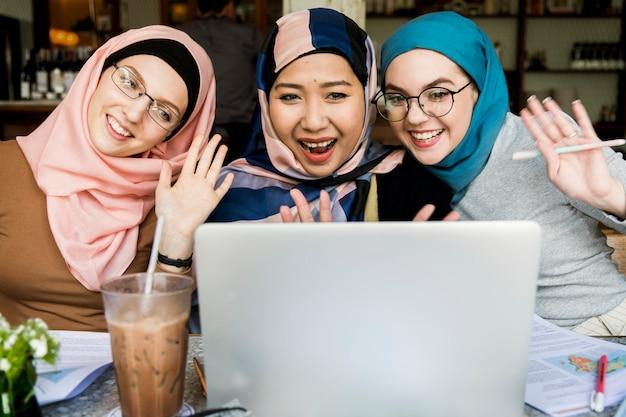 Islamitische vrouwenvrienden die laptop voor videovraag met behulp van