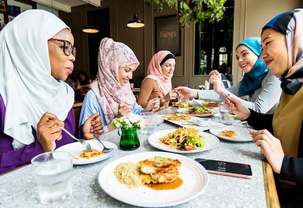 Islamitische vrouwenvrienden die samen met geluk dineren
