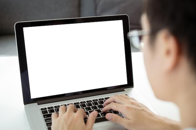 Isolatie met uitknippad. jonge zakenman die achter de laptopcomputer werkt tijdens de quarantaine of zelfisolatie. zakenman met behulp van notebookcomputer om te werken. leeg notebookscherm.