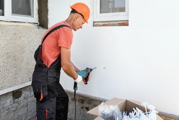 Isolatie van het huis met polyfoam. de arbeider boort gaten om de piepschuimplaat aan de gevel te bevestigen.