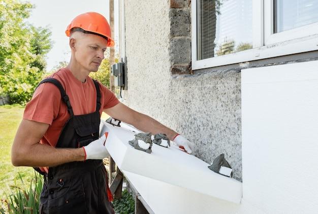 Isolatie van het huis met polyfoam. de arbeider plaatst een piepschuimplaat op de gevel.