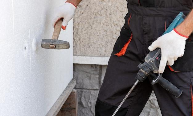 Isolatie van het huis met polyfoam. een werknemer gebruikt een hamer voor deuvels die polystyreenplaten bevestigen.