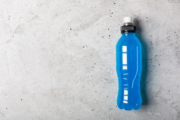 Isotone energiedrank. flessen met blauwe transparante vloeistof, sportdrank op een grijze betonnen achtergrond