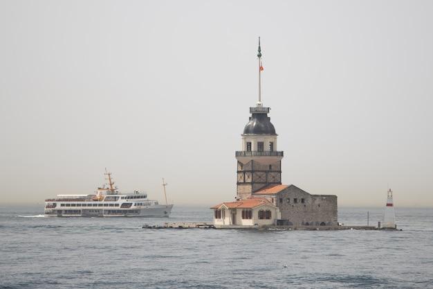 Istanboel, turkije - augustus 08, 2021: een mening van istanboel maiden tower kiz kulesi en boot in bosporus