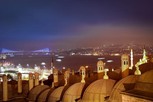 Istanbul. nacht. bewolkt. uitzicht op de bosporus-straat, de galata-brug, de bosporus-brug en de daken van medrese-i rabi. veel schepen