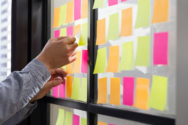It-medewerker die zijn taken op het kanban-bord volgt. taakbesturing van agile ontwikkelingsmethodologie gebruiken. mens die kleverige nota vastmaken aan scrumtaakraad in het bureau