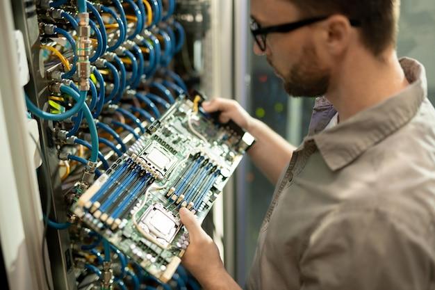 It-ondersteuningsspecialist die het moederbord van de server onderzoekt