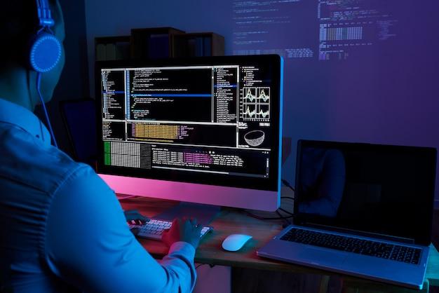 It-specialist die code controleert bij computer in het donkere kantoor 's nachts