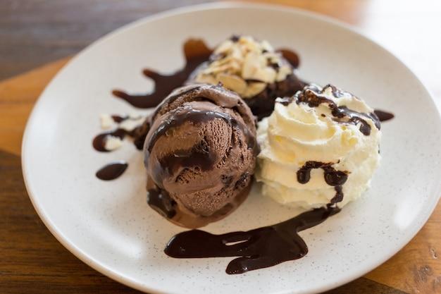 Italiaans chocolade-ijs met brownies en slagroom gegarneerd met chocolade op een witte plaat.