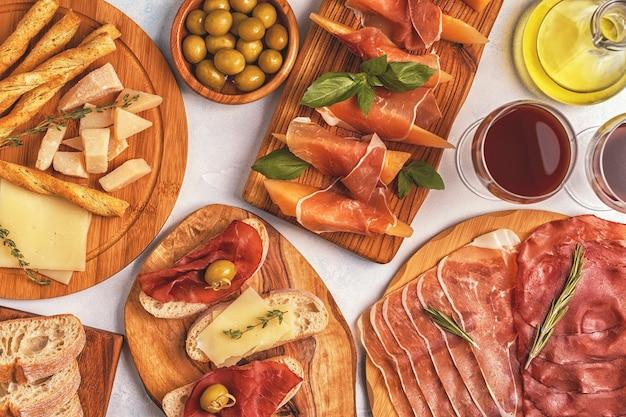 Italiaans eten achtergrond met ham, kaas, olijven, brood en wijn