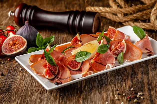 Italiaans eten. antipasti-voorgerecht met prosciutto, vijgen en basilicum. serveert gerechten in een restaurant in een witte plaat op een houten tafel
