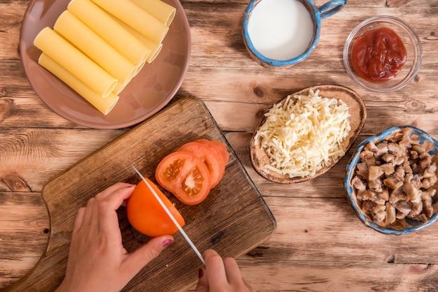 Italiaans eten concept. ingrediënten voor het koken van pasta. droge cannelloniendeegwaren, kersentomaten, verse basilicum, knoflook op zwarte backraund.