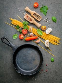 Italiaans eten en menu concept spaghetti met ingrediënten op donkere tafel.