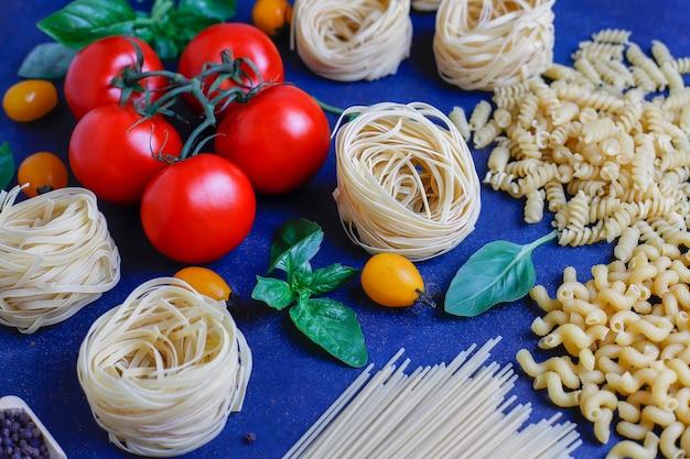 Italiaans eten . italiaanse keuken. ingrediënten tomaten, gele kerstomaten, verse basilicum, zwarte peperkorrels, verschillende pasta.