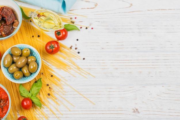 Italiaans eten kookconcept. ingrediënten voor de spaghetti van voorbereidingsdeegwaren - tomaat, olijfolie, kruiden, kruiden, groene olijven, tomatensaus, witte houten achtergrond. bovenaanzicht met kopieerruimte voor tekst