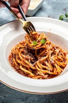 Italiaans eten. pasta spaghetti met tomaat en vlees gehakt saus geserveerd in een bord met parmezaanse kaas op vork. verticaal beeld.