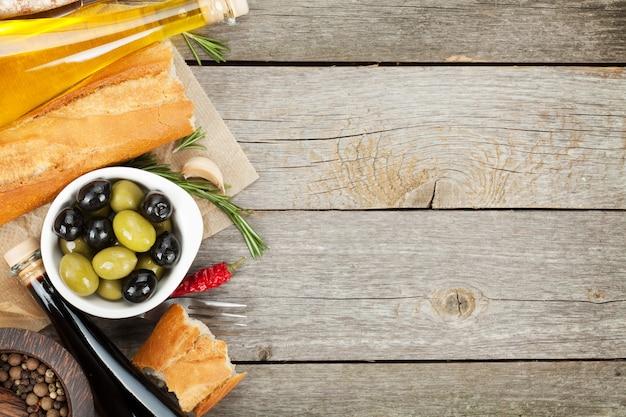 Italiaans eten voorgerecht van olijven, brood en kruiden op houten tafel achtergrond met kopieerruimte