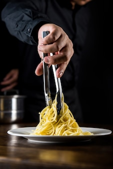 Italiaans pasta spaghetti eten wordt gekookt en geplateerd door chef-kok