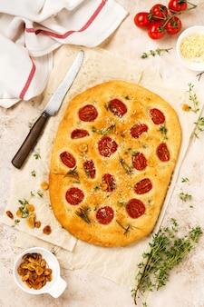 Italiaans traditioneel focacciabrood bakken met met kerstomaatjes, parmezaanse kaas en rozemarijn op lichtbruine achtergrond. bovenaanzicht