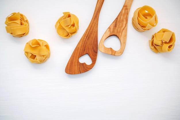 Italiaans voedselconcept en menuontwerp. fettuccine met hartvormige houten spatel.