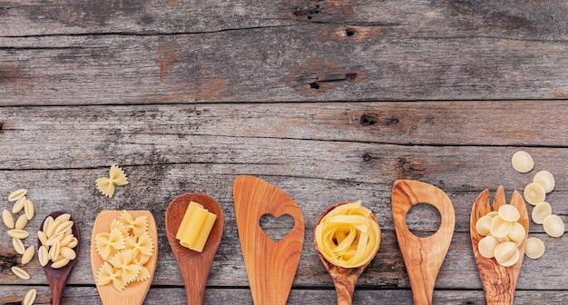 Italiaans voedselconcept en menuontwerp. verschillende soorten pasta elleboog macaroni, farfalle, rigatoni, gnocco sardo in houten lepels setup op houten achtergrond.