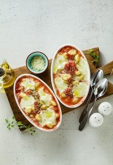 Italiaanse aardappel knoedels gnocchi alla sorrentina met mozzarella kaas, gebakken in de oven met tomatensaus en kruiden.