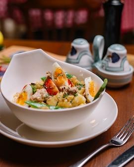 Italiaanse aardappelsalade met tonijnbonen, cherrytomaat, peterselie, gekookte eieren en olijfolie