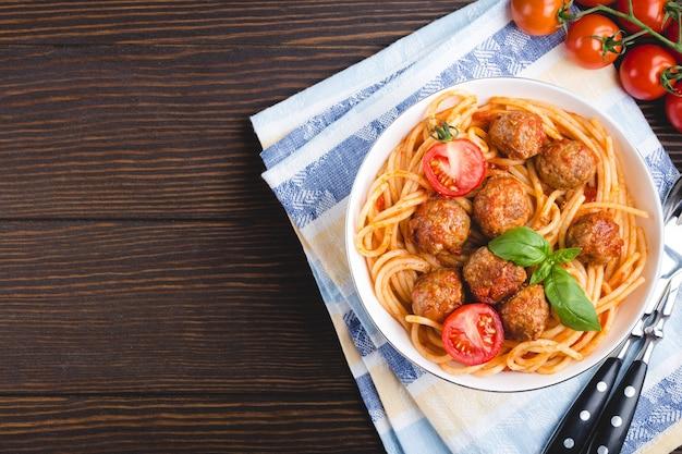 Italiaanse amerikaanse traditionele schotelspaghetti met gehaktballen, tomatensaus en basilicum in kom, rustieke houten achtergrond.