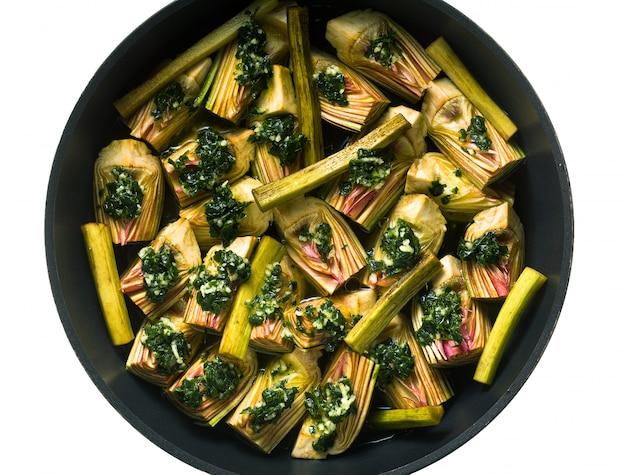 Italiaanse artisjokken koken in een pan met een saus van olijfolie, citroensap en peterselie.