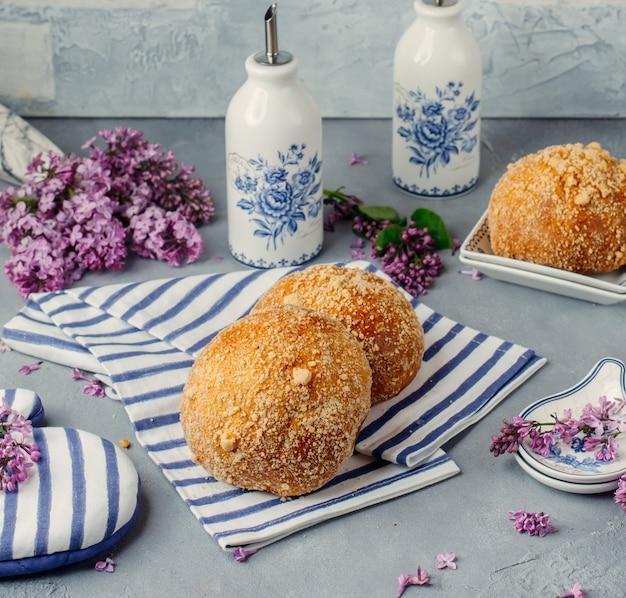 Italiaanse bomboloni op een tissue met bloemen rond.