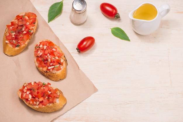 Italiaanse bruschetta met geroosterde tomaten, mozzarella kaas en kruiden op papier