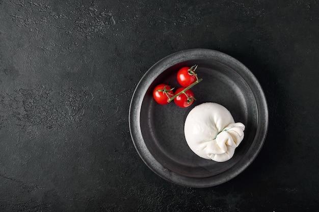 Italiaanse burrata kaas en tak van cherrytomaatjes op donkere plaat bovenaanzicht kopie ruimte