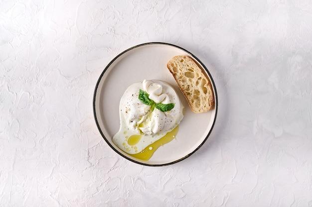 Italiaanse burrata kaas met ciabatta brood en olijfolie op witte plaat bovenaanzicht kopie ruimte