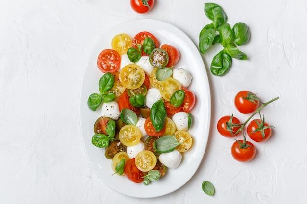 Italiaanse caprese salade met gesneden tomaten, mozzarella kaas, basilicum, olijfolie in houten kom.
