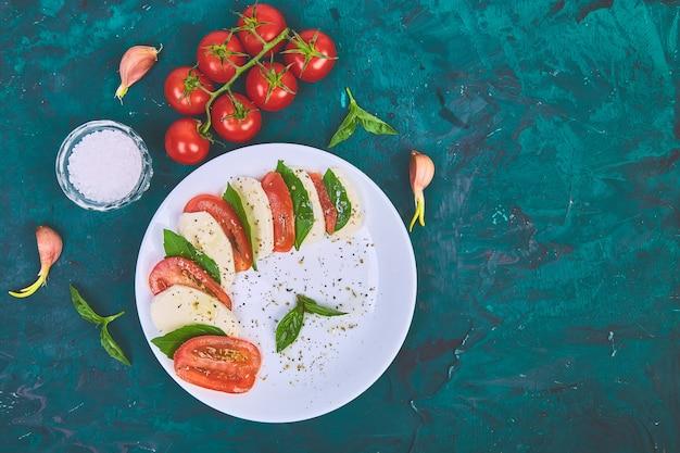 Italiaanse caprese salade met gesneden tomaten, mozzarellakaas, basilicum, olijfolie