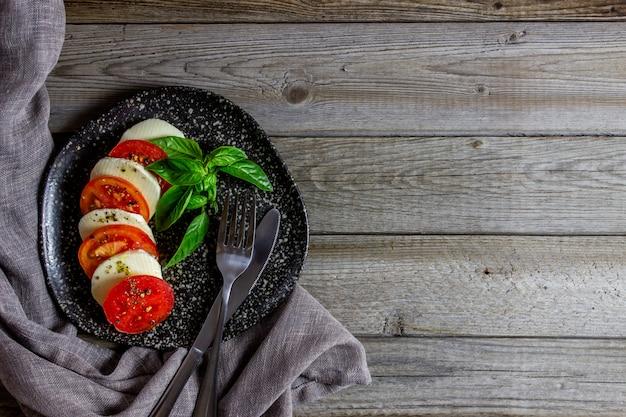 Italiaanse caprese salade met mozarella en tomaten. houten. gezond eten.