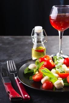 Italiaanse caprese salade met rode wijn, tomaten, verse biologische mozzarella en basilicum op stenen tafel