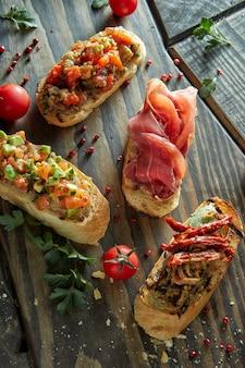 Italiaanse crostini met verschillende toppings op donkere houten tafel, bovenaanzicht