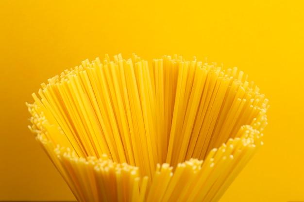 Italiaanse deegwaren op een gele keukenachtergrond. verse spaghettideegwaren om thuis te koken. pasta achtergrond