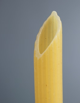 Italiaanse dichte omhooggaand van penne rigate macaroni pasta op grijs