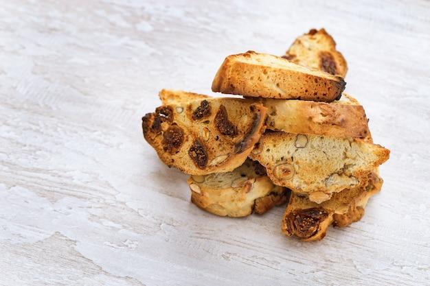 Italiaanse droge koekjesbiscotti met noten op houten lichte lijst.