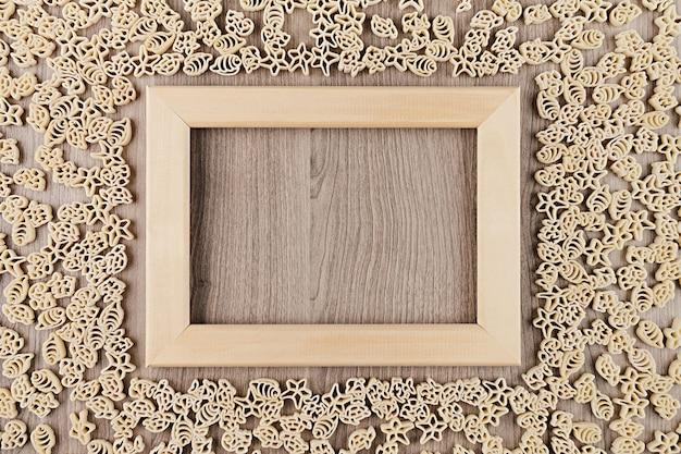 Italiaanse droge overzeese deegwaren op beige bruine houten raad met lege copyspace als decoratieve kaderachtergrond