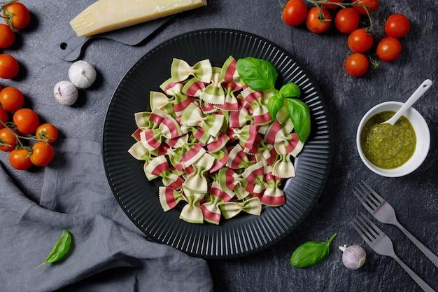Italiaanse farfalledeegwaren van verschillende kleuren, vlagkleuren, met kerstomaatjes, harde parmezaanse kaas, basilicum, pesto, knoflook op een donkere achtergrond.