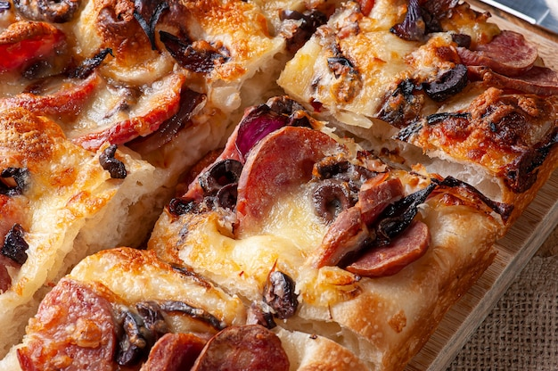 Italiaanse focaccia met pepperoniworst, zwarte olijven, parmezaanse kaas en ui