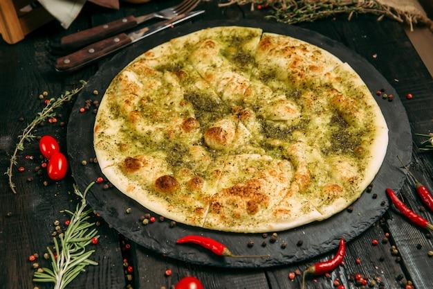 Italiaanse focacciatortilla met olijfolie op een zwarte raad op een donkere houten horizontale achtergrond ,.