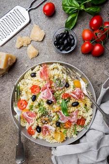 Italiaanse fusilli-spiraalvormige pasta met druiventomaten, olijven, parmaham en parmigiano kaas op een bord Premium Foto