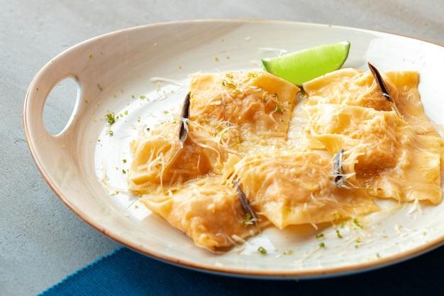 Italiaanse gerecht ravioli met parmezaanse kaas in een bord