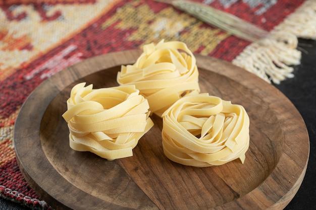 Italiaanse gerolde ongekookte fettuccine pasta op een houten bord met tarwe